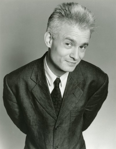 black and white photograph of a man in a suit leaning forward into the camera