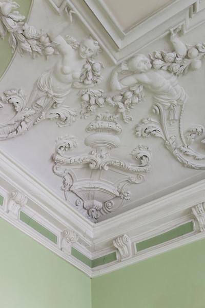 Stuckdecke des Grünen Saals — Eckreliefs mit Mischwesen und Girlanden — Weibliche und männliche Figur mit Girlande aus Früchten