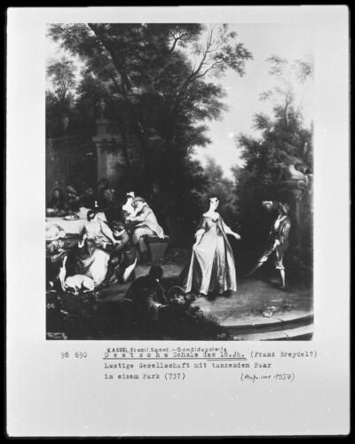 Lustige Gesellschaft mit tanzendem Paar in einem Park
