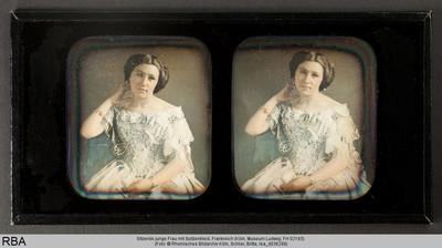 Sitzende junge Frau mit Spitzenkleid