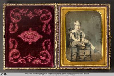 Junge auf Stuhl sitzend, das rechte Bein hochgezogen