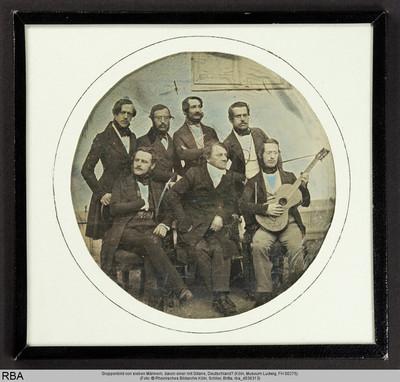 Gruppenbild von sieben Männern, davon einer mit Gitarre