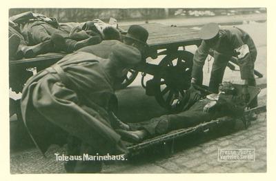 Tote aus Marinehaus.; drei Männer bahren einen Toten auf; im Hintergrund drei weitere Leichname auf einem Wagen