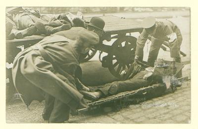 Novemberrevolution: Tote aus Marinehaus; drei Männer bahren einen Toten auf, hinter ihnen links drei weitere Leichen auf einem Wagen