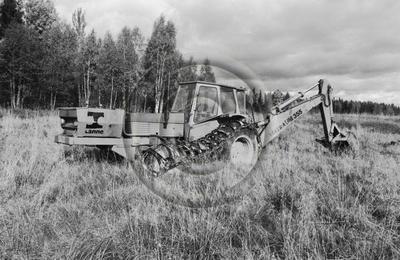 Valtra UM 355 -traktorikaivuri maanmuokkauksessa.