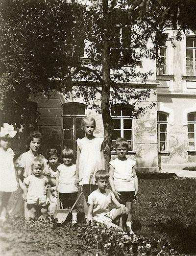 Kazė Vaitkienė sode su vaikais (šalia jos sūnus Vytis, priekyje tupi Rimgaudas). Kėdainiai, 1933 metai