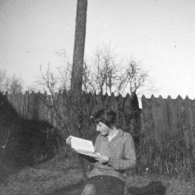 Marija Šikšnytė (1910–1945), skaitanti knygą sode prie namų. Vilnius, 1927 metai