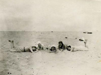 Gražutė su keturiom draugėmis Palangoje guli ant paplūdimio smėlio