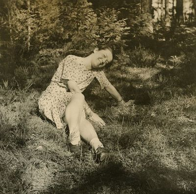 Gražutė Šlapelytė sėdi ant žolės eglyne