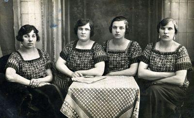 Keturių sėdinčių jaunų moterų vienodomis palaidinėmis portretas