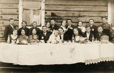 Vestuvininkai lauke prie vaišių stalo