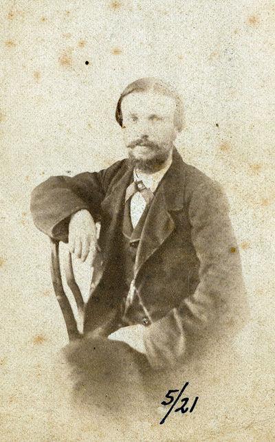 Vyro su ūsais ir barzda, sėdinčio ant kėdės, portretas