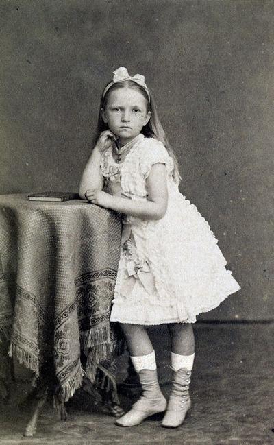 Mergaitės balta suknele ir kaspinu perrištais plaukais portretas