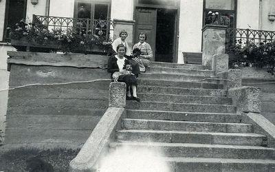 Moterų trijulė, sėdinti ant Kretingos dvaro rūmų paradinių laiptų