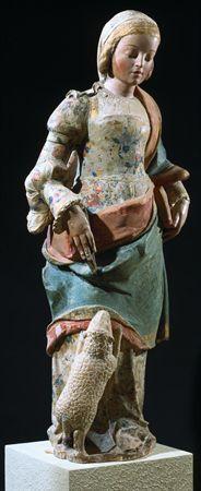 Escultura em calcário policromado representando Santa Inês em pé, brincando com um cordeirinho a seus pés, à direita. Está representada com um vestido florido, de corpete e envolta num manto. Tem o cabelo apartado ao meio, formando bandós e com uma coifa. Segura na mão esquerda um livro fechado.