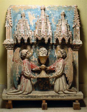 Retábulo em calcário poilicromado, representando o Corpo de Deus. É composto por uma única placa rectangular, que serve de fundo à cena representada: dois anjos ajoelhados elevam o cálice eucarístico, sobreposto pela hóstia com Cristo Crucificado. Os dois anjos e o cálice são coroados respectivamente, por três baldaquinos, sendo o central (o do cálice), ligeiramente maior; lateralmente, elevam-se dois pináculos, sobre capitel e mísula com motivos vegetalistas.Os anjos, destacando-se a meio-rele...
