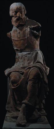 Escultura de vulto de um grupo escultórico não agregado, em barro cozido, representando a figura de um Apóstolo, sedente, pertencente a uma Última Ceia. Apresenta-se, em torção para a esquerda, com a cabeça ligeiramente voltada à direita. Tem o rosto marcado por olhos salientes, nariz longo, barba encaracolada e bifurcada, cabelo liso, com corte recto abaixo das orelhas, apartado a meio e com franja . Veste túnica abotoada e justa no peito, presa na cintura, caindo com pregas agrupadas sobre as ...