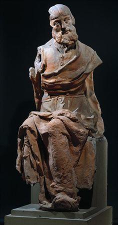 Escultura de vulto de um grupo escultórico não agregado, em barro cozido, representando a figura de um Apóstolo, sedente, pertencente a uma Última Ceia. Apresenta-se com a cabeça voltada à esquerda (mutilada), com o rosto afilado, malares salientes, nariz adunco, sobrancelhas finas, barba ondulada e cabelo liso com franja recta e risco ao meio. Veste túnica abotoada por dois grandes botões, justa no peito, presa na cintura com cinto fino, com pregas agrupadas sobre as pernas caindo sobre o pé es...