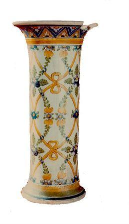 Jarra moldada de forma cilíndrica em faiança branca vidrada e decorada a azul, amarelo e verde, predominantemente. O bordo não apresenta qualquer tipo de decoração e o bocal, largo e saliente para o exterior, apresenta uma barra azul de motivos geométricos triangulares, em azul e amarelo, nos quais se inserem flores e uma cercadura amarela. O bojo é totalmente decorado com grinaldas de folhagem e flores (amarelas,azuis e verdes) que se entrelaçam entre si interseccionando-se com grinaldas de l...
