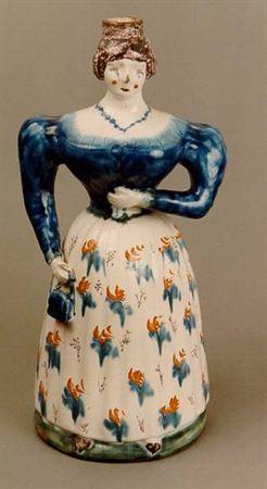 Garrafa antropomórfica de faiança policromada e esmaltada a branco. A figura feminina apresenta cabelos castanhos apanhados e face delicada de bochechas vermelhas. Ostenta um colar de pérolas em contraste com a alvez da derme e traja blusa azul, de mangas compridas de balão e saia longa e franzida, de tecido alvo decorado com motivos florais e vegetalistas, de policromia azul e vermelha. A sinistra repousa no tronco, enquanto a dextra ostenta mala azul. Apresenta base circular. Artur de Sandão, ...