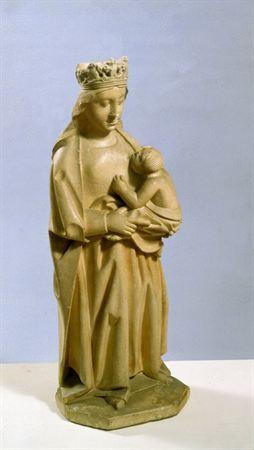 Escultura de vulto pleno, em calcário brando, representando Nossa Senhora de pé, posição frontal, amamentando o Menino Jesus. A Virgem apresenta-se coroada, cabelos soltos pelos ombros e costas, túnica de decote trapezoidal e manto roçagante. Sustenta o Menino Jesus no braço esquerdo. Este encontra-se de tronco desnudo, mãos sobre o peito da mãe, boca pousada no seu seio. As pregas do manto de Nossa Senhora são profundamente cavadas, interrompidas e verticais, e dobram para fora sobre a base, ...