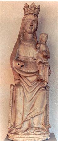 Escultura de meio vulto representando Nossa Senhora com o Menino, assente em base circular decorada com faixa geométrica. Os cabelos ondulados molduram a face alongada de Nossa Senhora. A cabeça possui coroa flordelizada colocada sobre manto roçagante, orlado com motivos geométricos, que cai em pregas quebradas a meio. Traja túnica roçagante cintada com duas barras de decoração geométrica. A Virgem calçada segura no braço esquerdo o Menino, que enverga túnica cintada e longa, deixando-lhe os pés...