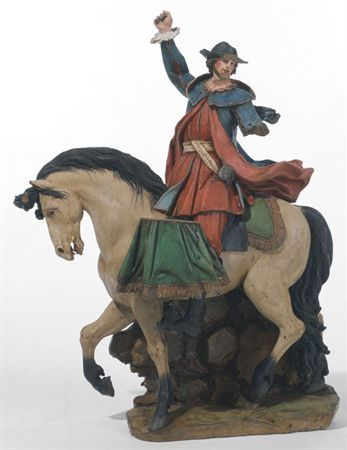 Figura policroma. Cavaleiro de perfil, jovem, erguendo o braço direito, com a cabeça em torção sobre o ombro esquerdo. Traja uma indumentária semelhante à dos cavaleiros que o antecedem (os trombeteiros). Traja chapéu, casaco do qual pende, à esquerda, uma espada, calções e botas altas. O cavalo segue a trote, tendo suspenso do dorso, lateralmente, um tambor.