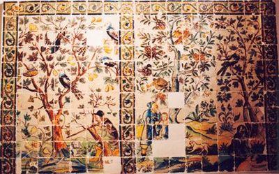 Painel de azulejos (11x18) policromo nas cores azul, amarelo, verde, ocre e maganês. Painel de dupla cena, uma de caça e outra pastoril. Figura na da esquerda, uma árvore ao centro, onde repousam aves, e à esquerda, um caçador acompanhado de um cão, apoiado numa árvore, dispara. Na cena da direita, duas árvores com aves empoleiradas, um pastor e criança (?) à esquerda, e à direita um animal(?). A cercadura de ramos espinhosos ondulantes terminando em flores, limita em cima e lateralmente o p...