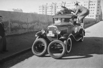 Gasógenos & Autoreportage [Gasógenos y reportaje de automóviles. Taxista colocando equipajes en la baca del coche y llantas apoyadas en el parachoques]