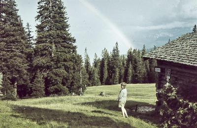 [Vista de arco iris sobre paisaje arbolado con casa de piedra de a la derecha. Rodolfo, hijo del fotógrafo, de espaldas junto a la casa]