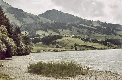 [Vista de lago con casas de tejado a dos aguas en la orilla y montañas al fondo]