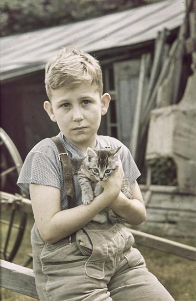 [Primer plano de Rodolfo sentado al aire libre con un gato entre sus brazos]