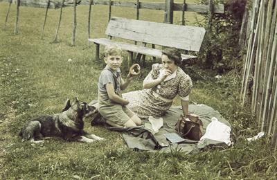 [Primer plano de Margarita, esposa del fotógrafo, sentada en una manta en el campo junto a su hijo Rodolfo comiendo un panecillo ante la atenta mirada de un perro tumbado junto a ellos]