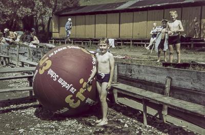 [Primer plano de Rodolfo, hijo del fotógrafo, junto a una pelota hinchable en un lago]