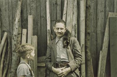 [Primer plano del fotógrafo Otto Wunderlich con un gato sobre su hombro izquierdo junto a su hijo Rodolfo]