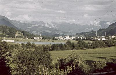 [Vista de una localidad junto a un lago y montañas al fondo]