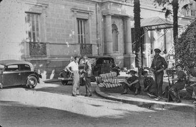[Vista de soldados sentados en la entrada de la Embajada Alemana en Madrid y dos hombres conversando junto a los coches aparacados]