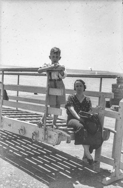 [Primer plano de Margarita, esposa del fotógrafo, sentada junto a su hijo cerca del mar]