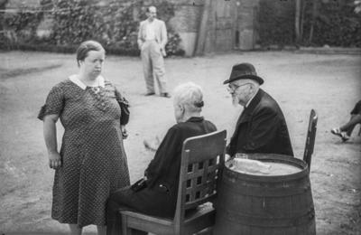 [Dos ancianos sentados junto a una mujer de pie en los jardines de la Embajada Alemana de Madrid refugiados tras el estallido de la Guerra Civil]