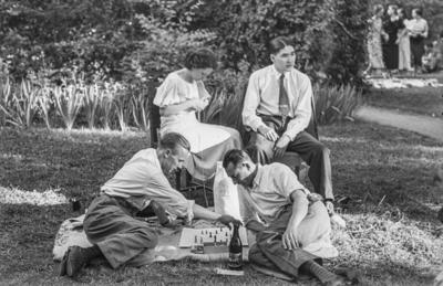 [Dos hombres sentados en el suelo jugando al ajedrez mientras una mujer cose sentada en una silla junto a otro hombre sentado en los jardines de la Embajada Alemana de Madrid refugiados tras el estallido de la Guerra Civil]