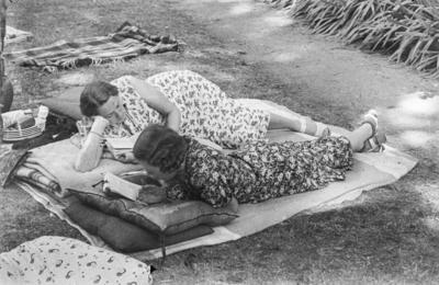 [Primer plano de dos mujeres leyendo tumbadas en una manta con cojines en los jardines de la Embajada Alemana de Madrid refugiadas tras el estallido de la Guerra Civil]
