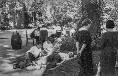 [Grupo de personas, unas sentadas, otras tumbadas y otras jugando a las cartas, en los jardines de la Embajada Alemana de Madrid tras ser evacuados con el estallido de la Guerra Civil]