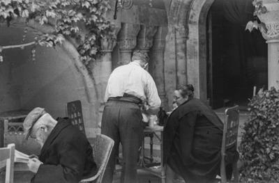 [Hombre sirviendo bebida a una mujer sentada en una mesa en los jardines de la Embajada Alemana de Madrid tras la evacuación por el estallido de la Guerra Civil]