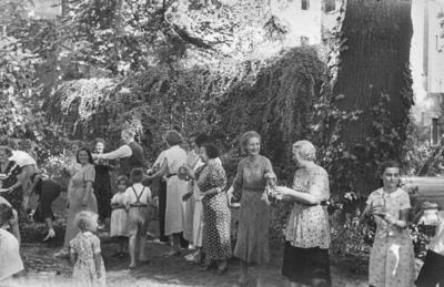 [Grupo de personas formando una cadena con tarros de cristal en las manos para coger agua en los jardines de la Embajada Alemana de Madrid tras ser evacuados con el estallido de la Guerra Civil]