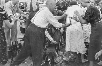 [Grupo de personas recogiendo agua de un depósito en los jardines de la Embajada Alemana de Madrid tras ser evacuados con el estallido de la Guerra Civil]