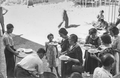 [Vista de Margarita, esposa del fotógrafo con un plato de comida en las manos esperando su turno para coger agua en los jardines de la Embajada Alemana de Madrid tras el estallido de la Guerra Civil]