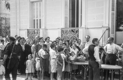 [Grupo de personas esperando turno para obtener un plato de comida en los jardines de la Embajada Alemana de Madrid tras el estallido de la Guerra Civil]