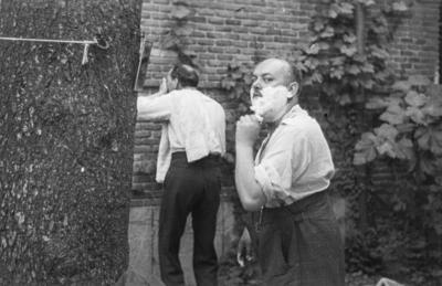 [Primer plano de un hombre afeitándose ayudándose de un espejo sujeto con un clavo en un árbol en los jardines de la Embajada Alemana de Madrid tras es estallido de la Guerra Civil]