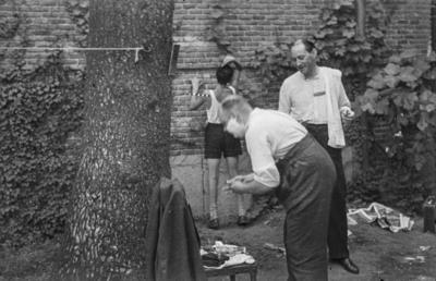 [Vista de hombre afeitándose y joven peinándose al fondo en los jardines de la Embajada Alemana de Madrid tras es estallido de la Guerra Civil]