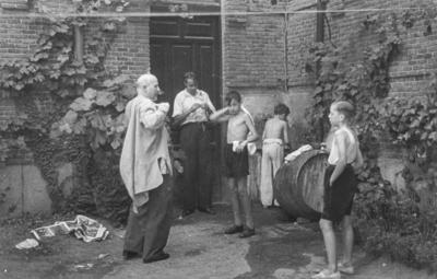 [Grupo de hombres y niños lavándose en uno de los rincones de los jardines de la Embajada Alemana de Madrid tras es estallido de la Guerra Civil]